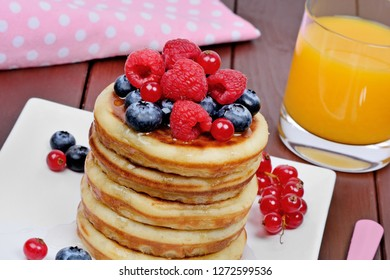 Close up of pancakes in a plate with fresh berries and orange juice on wooden table