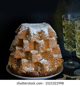 Close up of Pandoro, Italian Christmas cake with christmas decoration and champagne at the black background. Beautiful Xmas food concept.