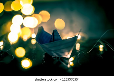 Close up of paper boat on wooden surface with reflection of Christmas decoration lights and decorative things.