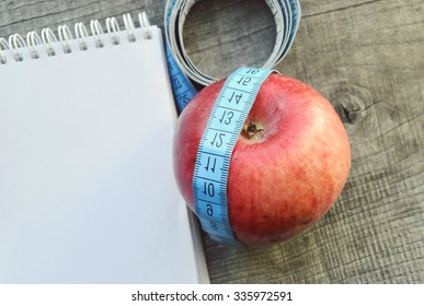 Close up of paper with diet plan, apple and measure tape on wooden table