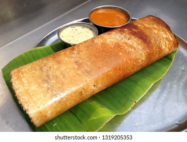 close up of paper masala dosa is a south indian meal served with sambhar and coconut chutney over fresh banana leaf.