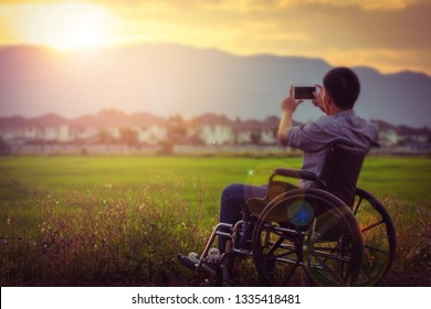 Close up of a paralyed man sitting on wheel chair took photo of the sunset by smart phone  at rice green field with blurred village and mountain background in the evening