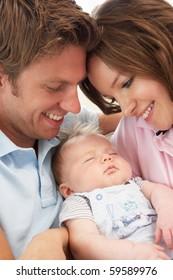 Close Up Of Parents Cuddling Newborn Baby Boy At Home