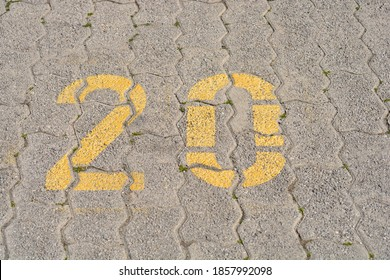 Close up of a parking spot with yellow number twenty