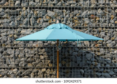 Close up part of big umbrella with gabion rock wall on background