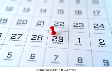 Close up of a part of the calendar of February and March, in black and white. A red pin is marking Leap Day - February 29.