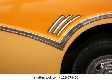 Close up of part of a yellow 1950's classic car, in Havana, Cuba.