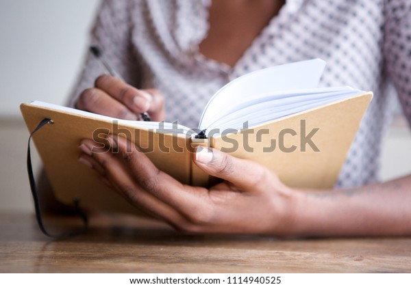 Close up partial portrait of black female author at home writing in journal