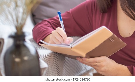 Close up partial portrait female author at home writing in journal