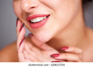 Close up partial portrait of woman smiling with red manicure and flawless complexion