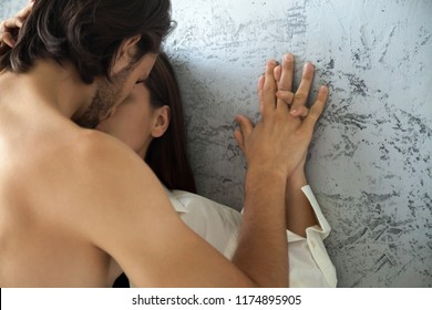 Close up of passionate couple hands hold together leaning on wall, sensual lovers enjoy intimate moment almost kissing, boyfriend and girlfriend enjoy foreplay touching and teasing, arousing desire