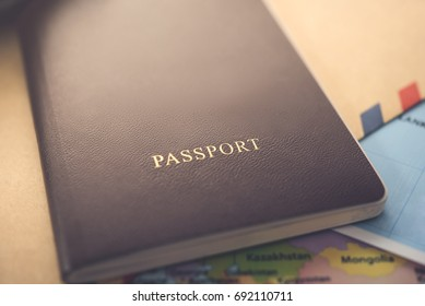 Close up of passport, brown cover, on the map and document prepared for traveling