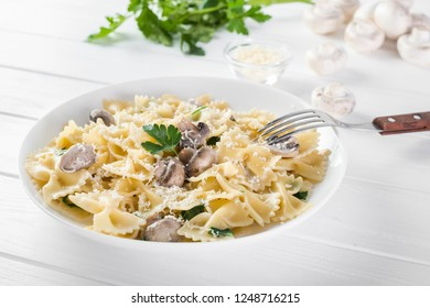 Close up pasta with mushroom and parsley on white wooden table.