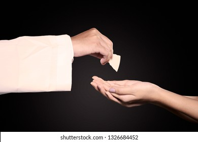 Close up of pastor giving first communion bread on woman hands in dark background