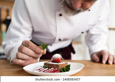 Close up pastry chef decoration delicious dessert dish, serving for customers in bakery, garnishing dessert plate with a mint leaf in commercial kitchen