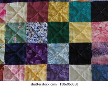 Close up of Patchwork Charm Squares Quilt and Hand Quilting