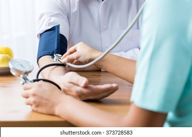 Close up of patient and doctor taking blood pressure