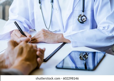 close up of patient and doctor taking notes in a hospital or clinic.