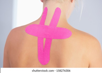Close up of patients back with applied kinesio tape in bright office