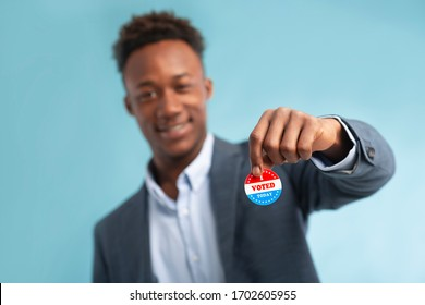 Close up of patriotic campaign button in hand of african american businessman voter, elections in USA 2020, blurred background