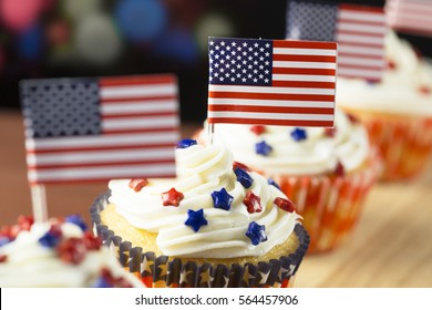 Close up of patriotic cup cake with red white and blue star topping and American flag. Shallow depth of field.