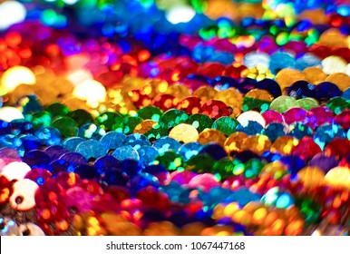 Close up of pattern made of colorful rainbow sequins shimmering and sparkling.