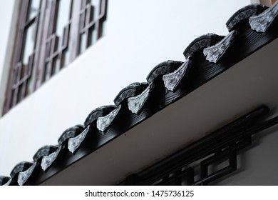 close up patterned eave of ancient Chinese old town with rain drops. White wall and wooden window blur background