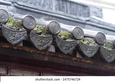 close up patterned eaves of ancient Asian house with green moss on it. Bright blur background