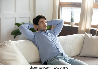 Close up peaceful young man relaxing with closed eyes on couch, leaning back with hands behind head, taking nap, sleeping or daydreaming, enjoying lazy weekend, leisure time, breathing fresh air