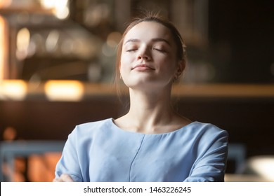 Close up of peaceful young woman relax lean back sitting with eyes closed dreaming or visualizing, happy calm female dreamer rest meditating controlling emotions. Stress free, mindfulness concept