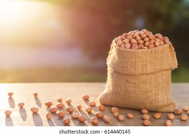 Close up peanut in small sack on wooden table. Outdoor shooting with sunlight and blur background.
