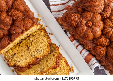 Close up of pecan pumpkin bread on white plate shot from above with uncut loaf on side