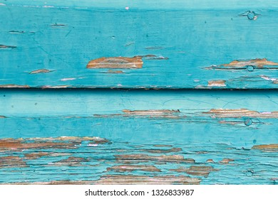 close up of peeling weathered turquoise paint on rustic wood