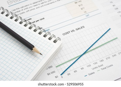 Close up of pen with financial graphs