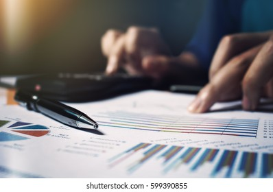 Close up pen on paperwork and woman hand calculate finance.