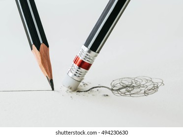 Close up of a pencil eraser removing a crooked line and the close up of a sharpened pencil writing a straight line.