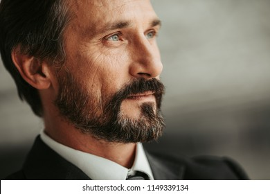 Close up pensive bearded businessman face looking away. Employer dreaming during job concept