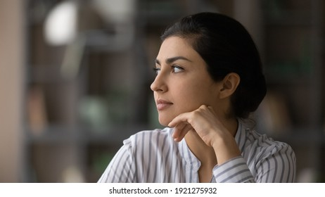 Close up of pensive Indian woman look in distance thinking pondering or life choices make solution. Thoughtful millennial mixed race ethnicity female decide or plan. Visualization concept.