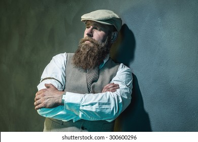 Close up Pensive Middle Aged Bearded Man with Flat Hat Leaning Against Wall with Arms Crossed and Looking Into the Distance.
