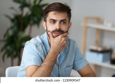 Close up of pensive millennial man sit at office home desk thinking of problem solution, thoughtful male lost in thoughts ponder or consider plan implementation, guy look in distance making decision