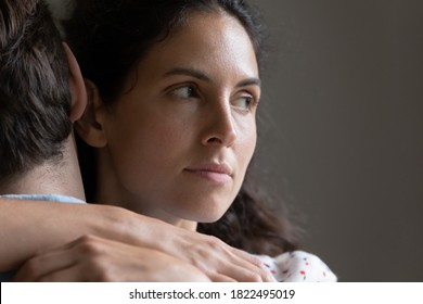 Close up of pensive woman hug man feel skeptical look in distance think of cheating in relationships. Suspicious unfaithful female embrace husband pondering of marriage problems or family troubles.