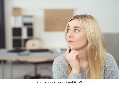 Close up Pensive Young Woman with Long Blond Hair Holding a Pen While Looking Upper Left of the Frame.