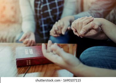 Close up of  people group holding a hand and pray together over a blurred holy bible on wooden table, Christian fellowship  or praying meeting in home concept with copy space