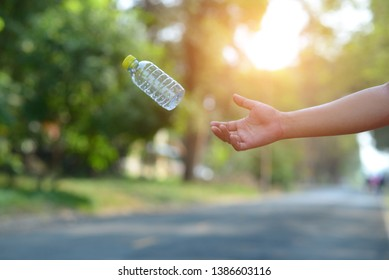Close up people hand holding throwing empty plastic bottle then throw away in the park with sunlight.Do not waste the garbage concept.