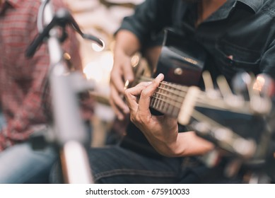 Close up people hand playing a guitar in selective focus with vintage tone.