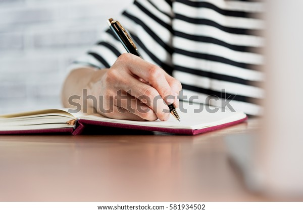 Close up of  people hand  writing on notebook on wooden table