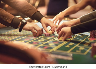 Close up of people hands laying chips on roulette table in casino.