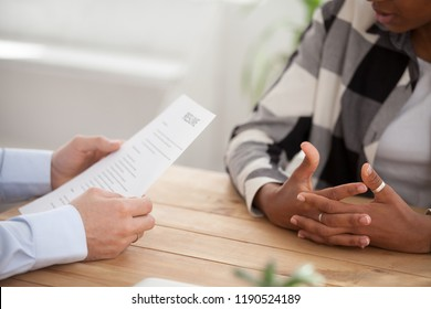 Close up people hands on a wooden table, boss and candidate woman during interview. Director hr manager holding resume paper, african woman talking about yourself. HR recruitment and hiring concept