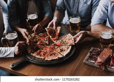 Close up of People Hands Taking Slices of Pizza. Smiling Friends Eating Pizza and Drinking Beer at Restaurant or Pizzeria. Friends Partying and Eating Pizza. Drinking Beer.