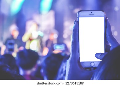 Close up of people holding their smart phones and capturing a video on a mobile phone at a music festival.